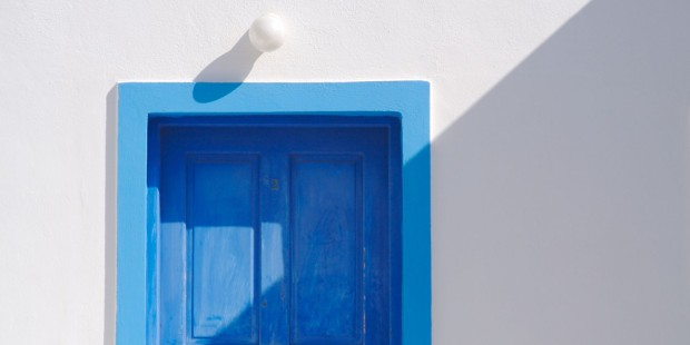 Abstract close-up of Santorini home wall, door and lamp.